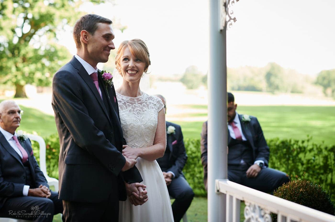 Bride and groom exchange vows during oudoor wedding at Pendrell Hall