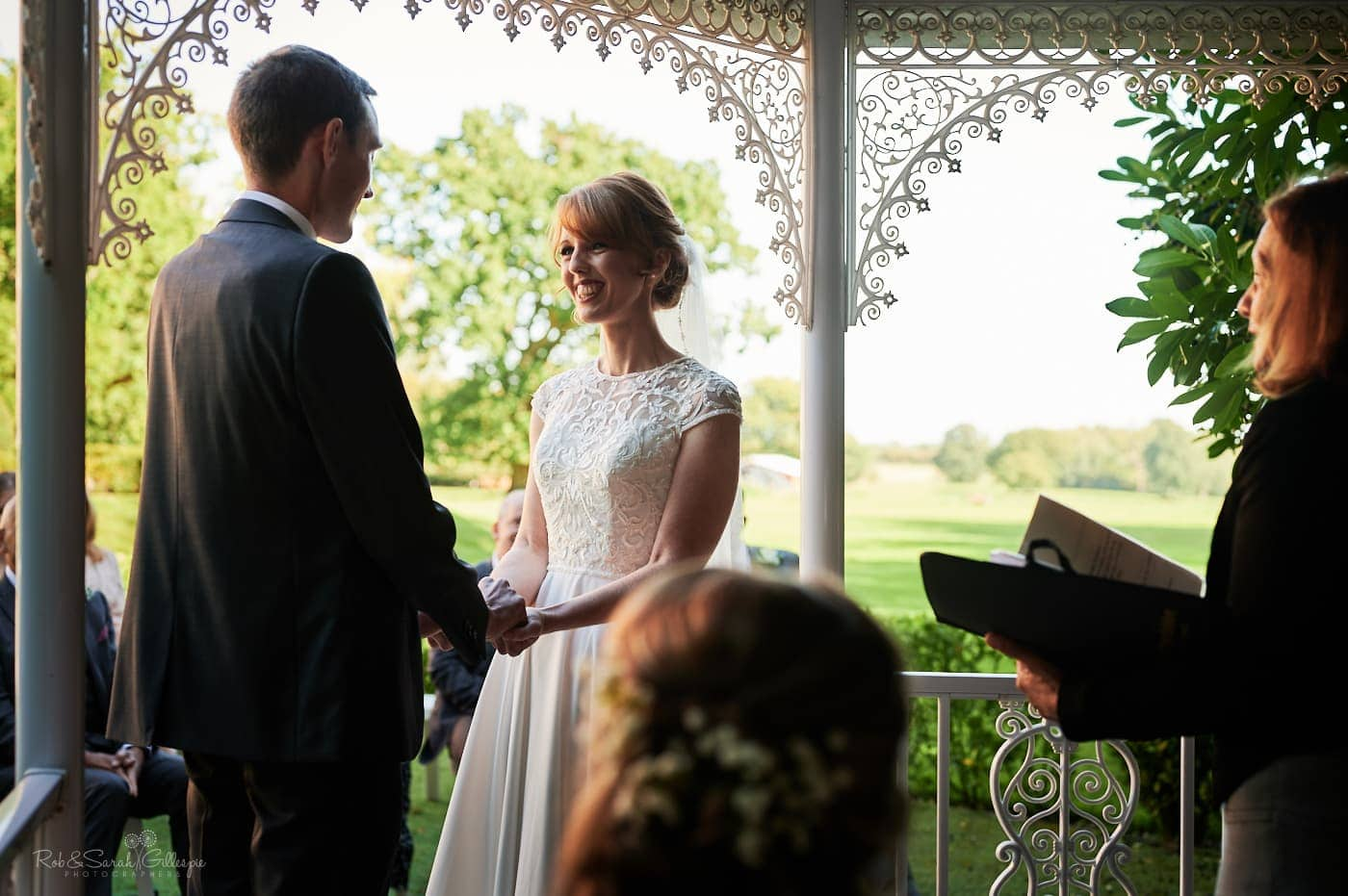Bride and groom hold hands as they exchange wedding vows