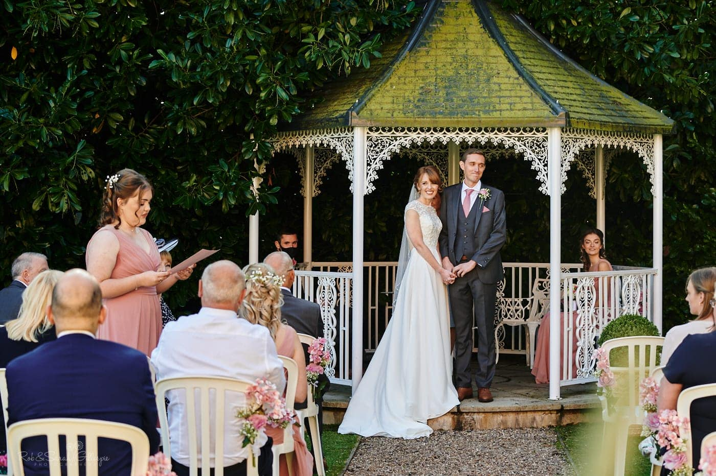 Bride and groom listen as bridesmaids gives reading