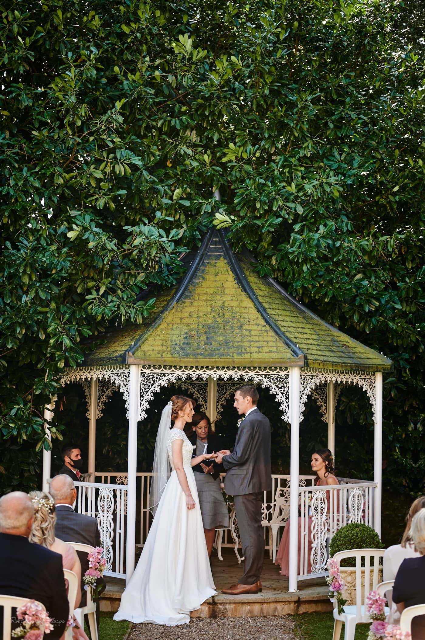 Bride and groom exchange wedding rings during outdoor ceremony at Pendrell Hall