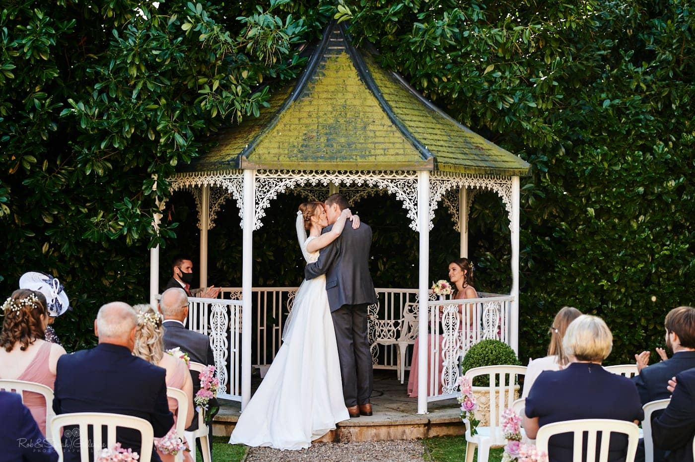 Bride and groom kiss during outdoor wedding