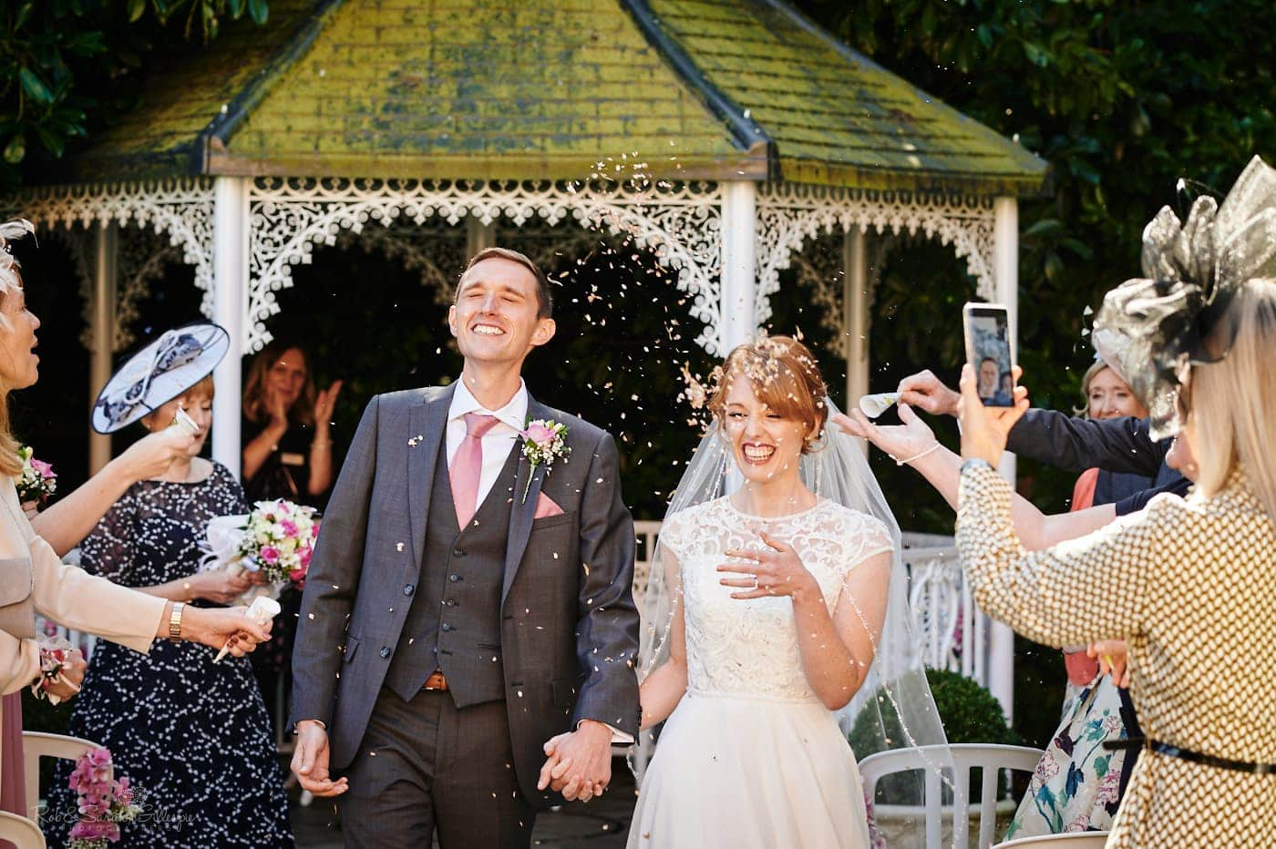 Bride and groom walk through confetti after outdoor ceremony at Pendrell Hall