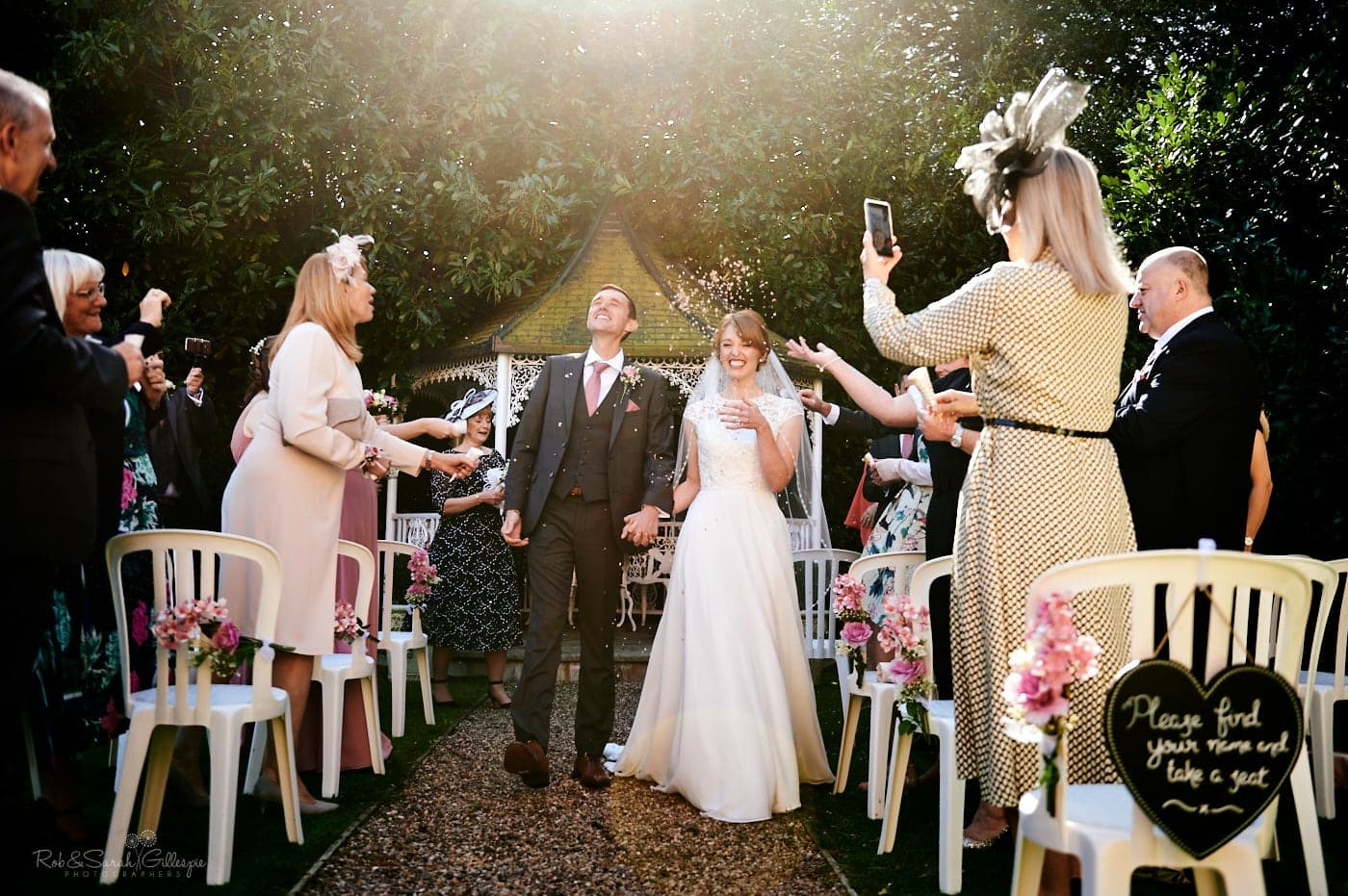 Bride and groom walking up aisle as wedding guests throw confetti
