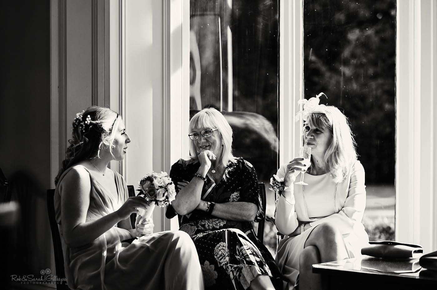 Wedding guests sit in strong sunlight as they chat