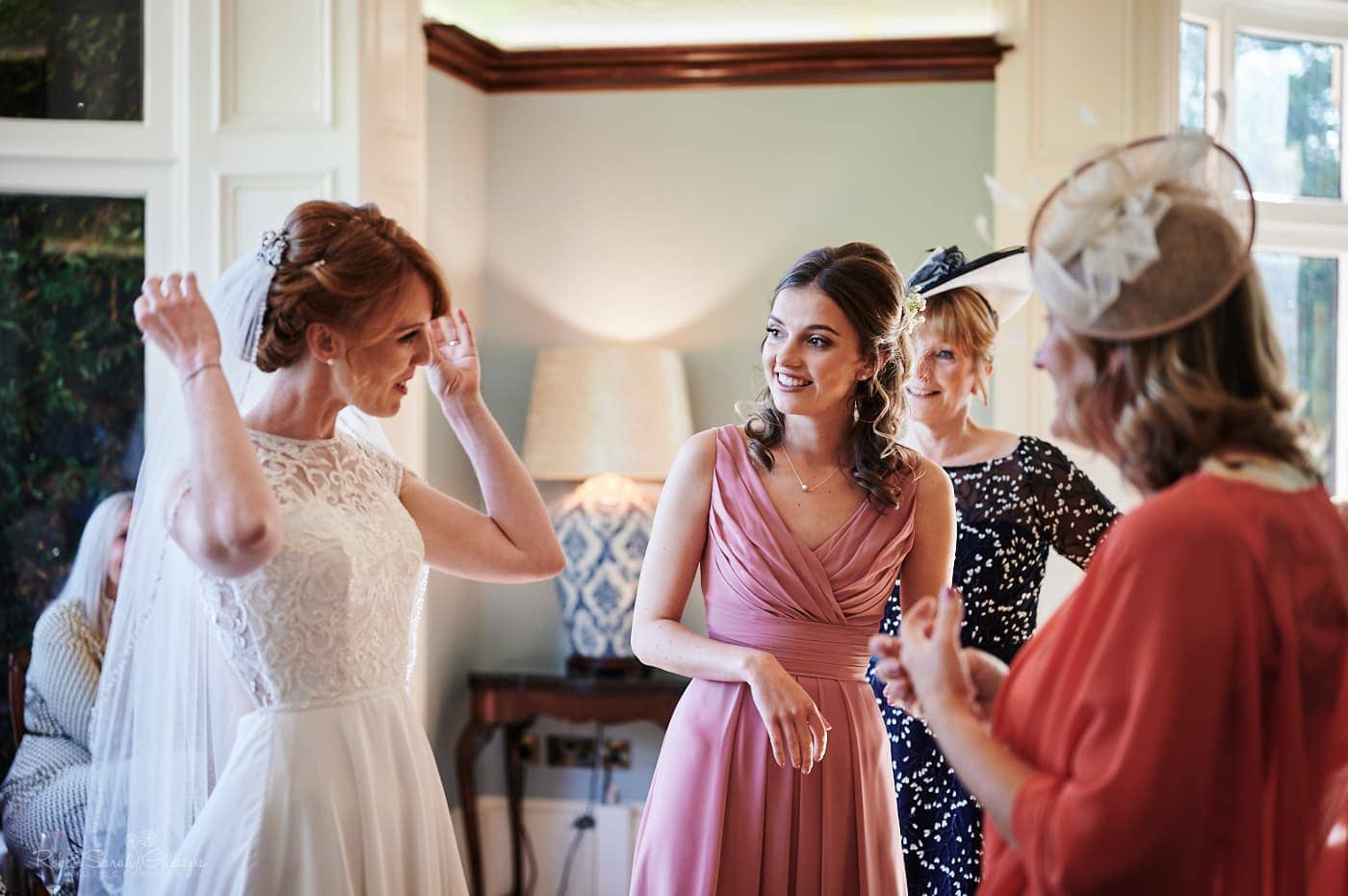 Bride and guests chat during small wedding drinks reception