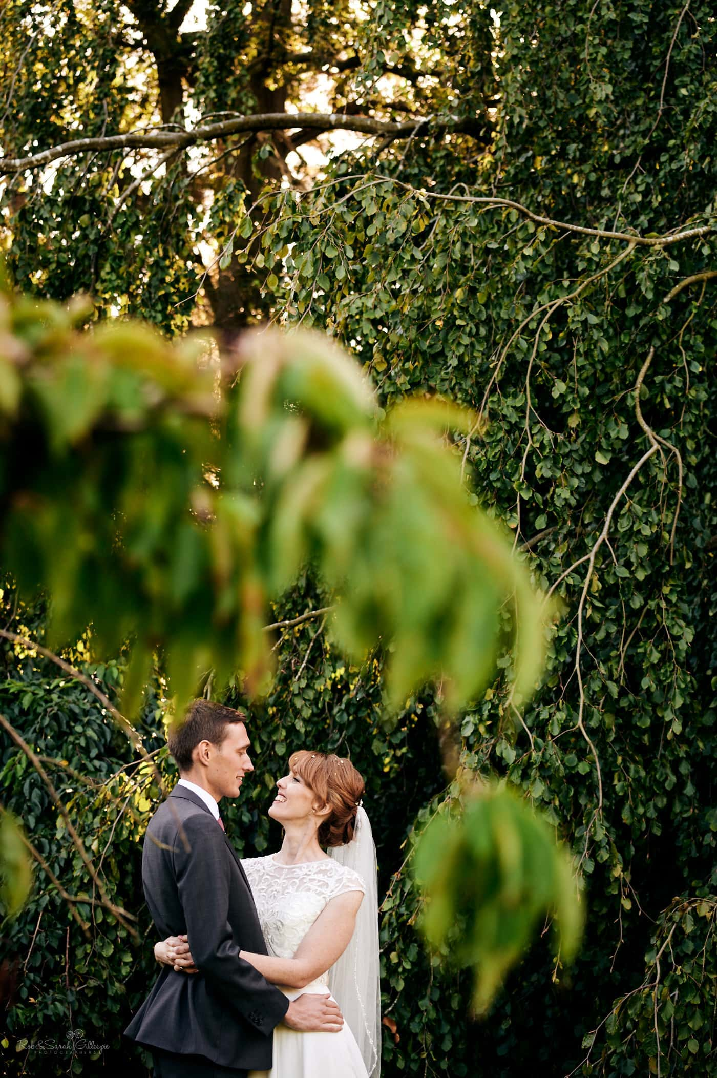 Bride and groom amongst low-hanging tree branches