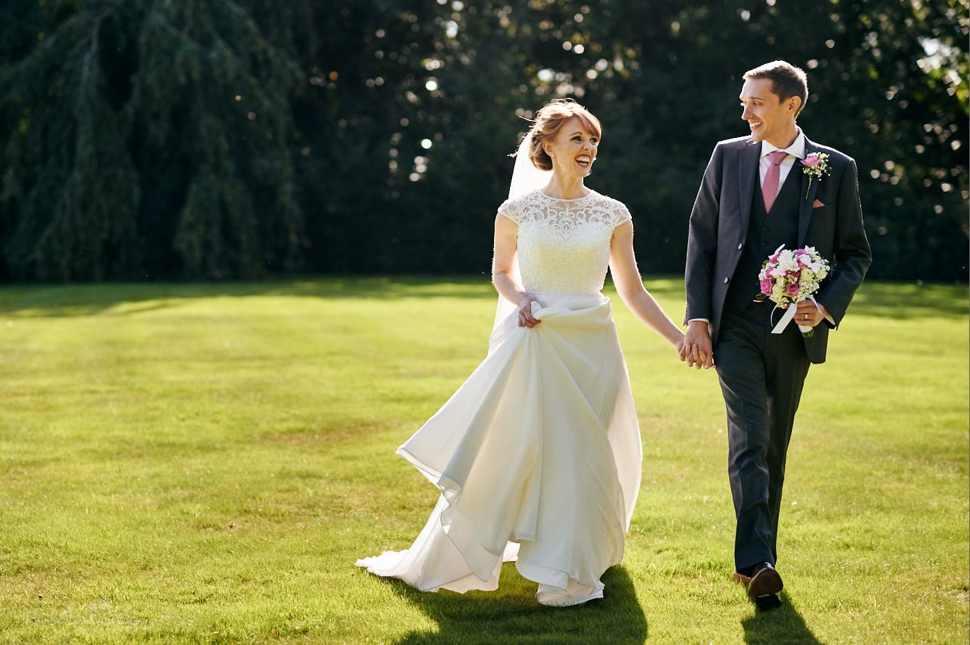 Bride and groom walk through gardens at Pendrell Hall