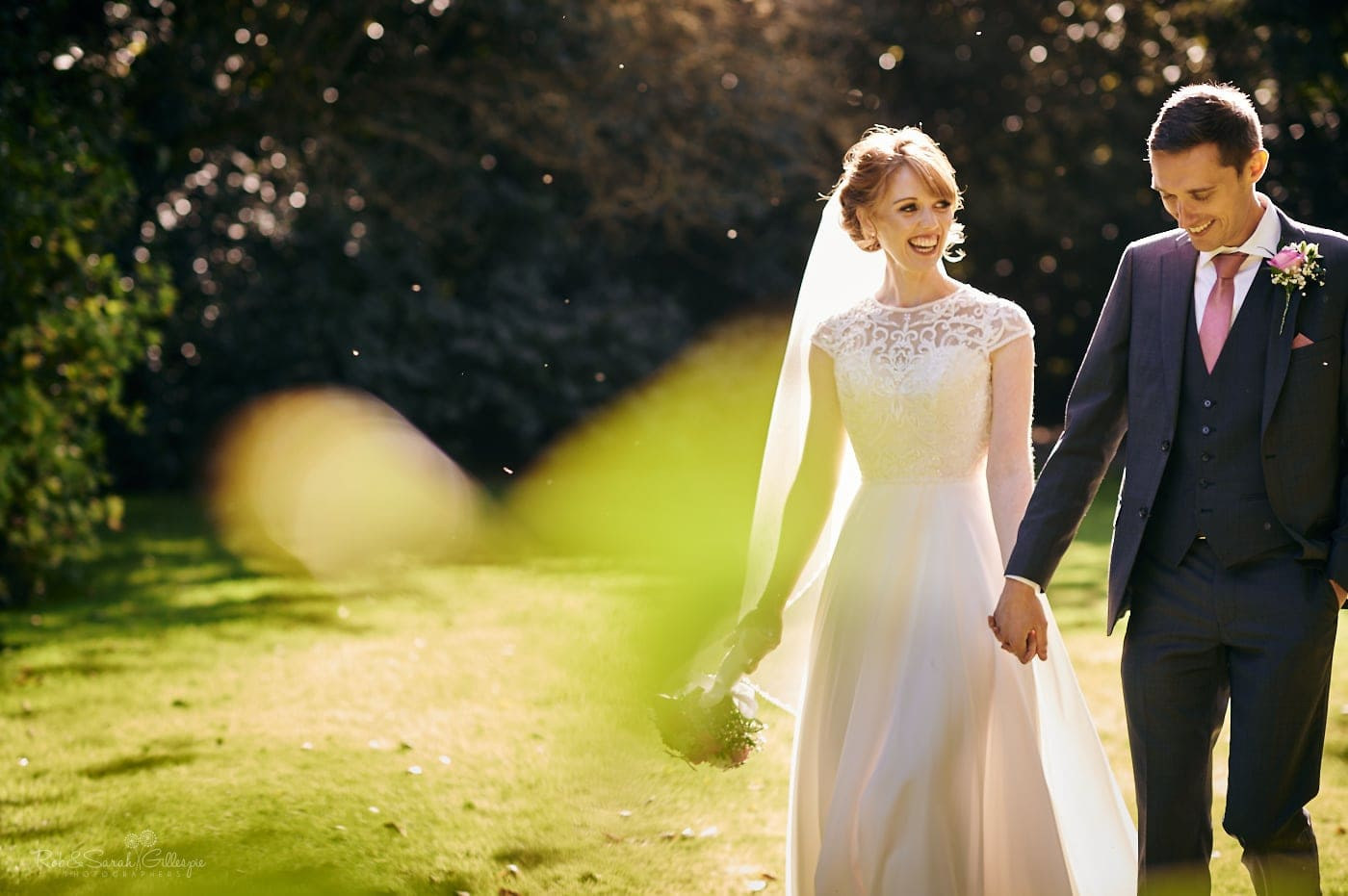 Bride and groom walk through beautiful gardens on sunny day at Pendrell Hall