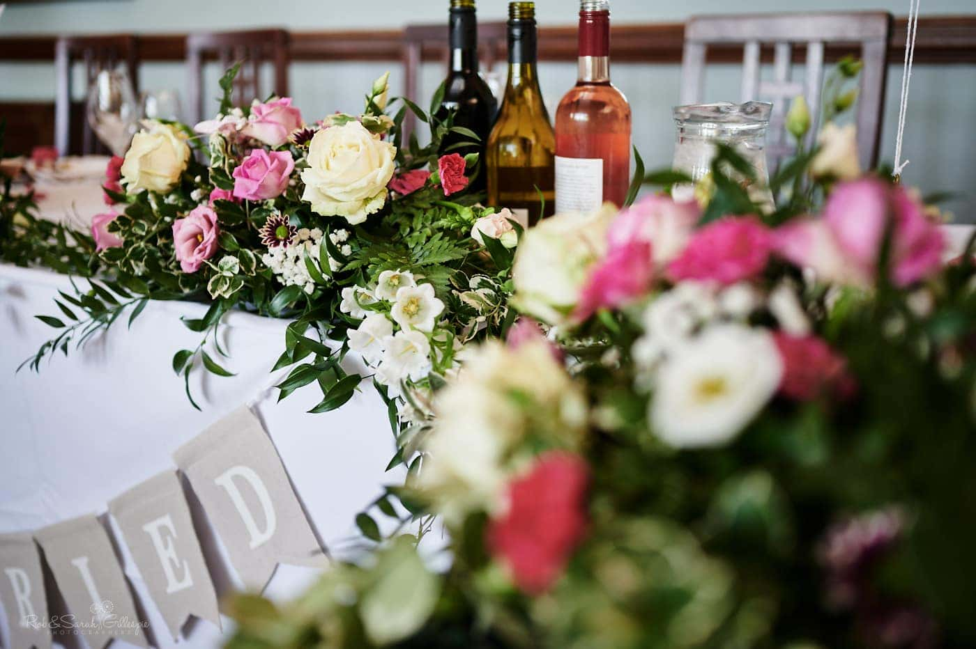 Flowers and wine bottles on table ready for wedding meal