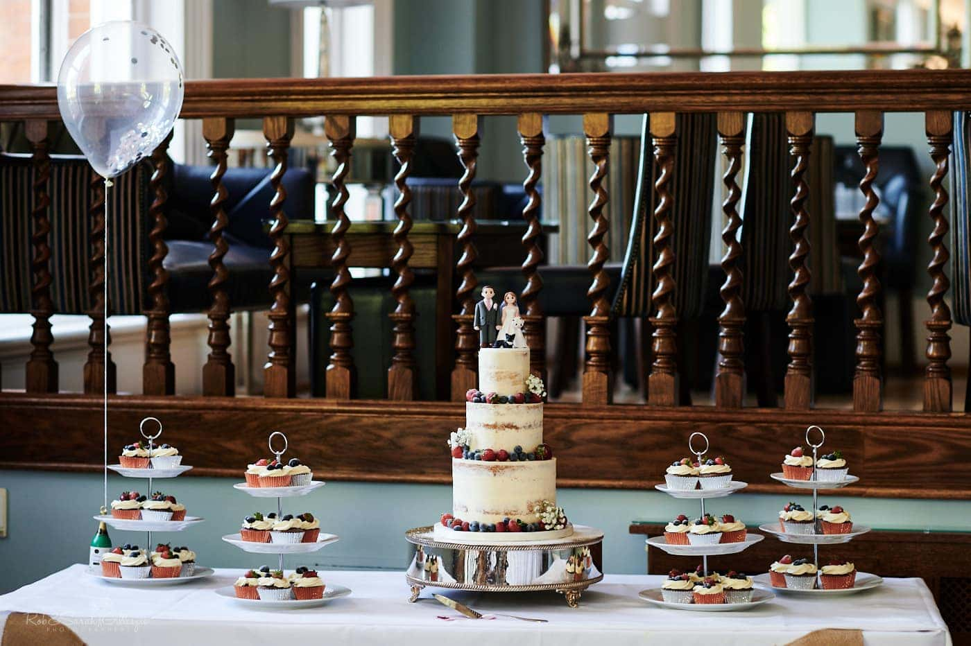Wedding cake with topper and smaller cupcakes