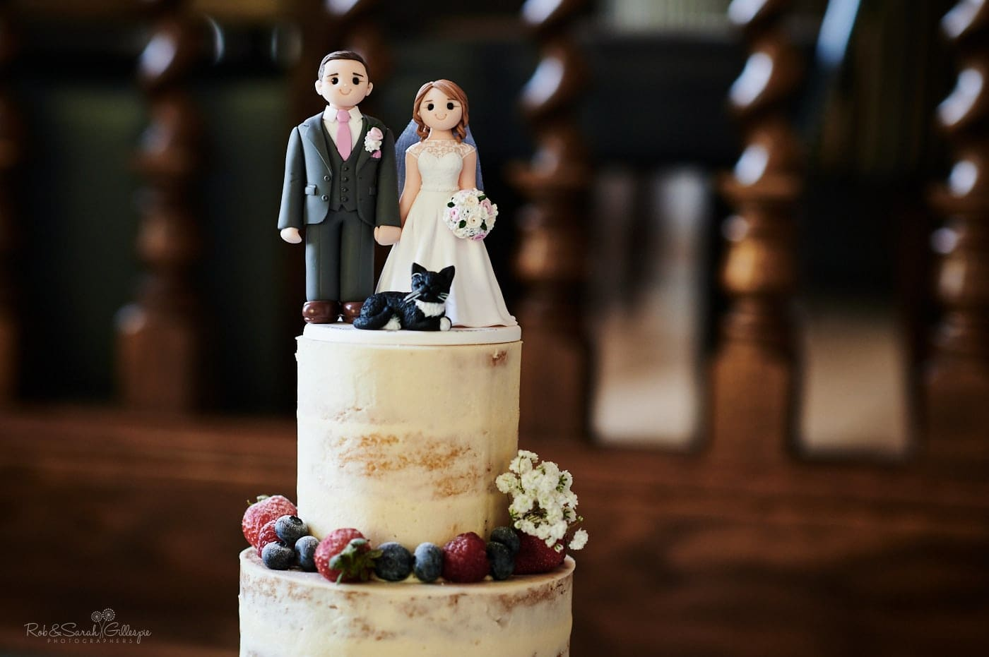 Wedding cake topper with bride, groom and black cat
