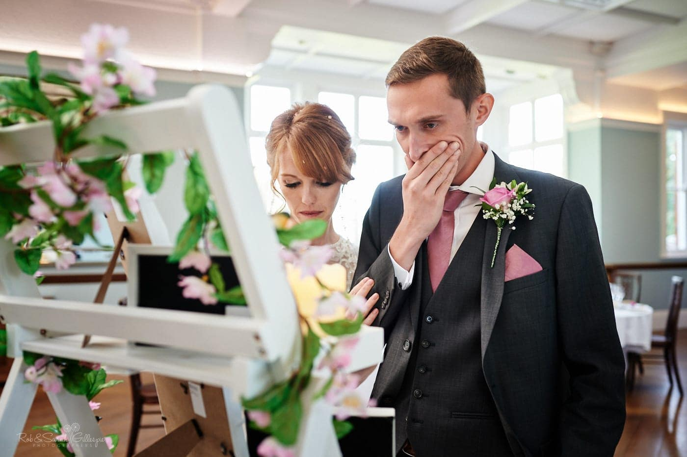 Groom emotional as he looks at photos of relatives at Pendrell Hall wedding