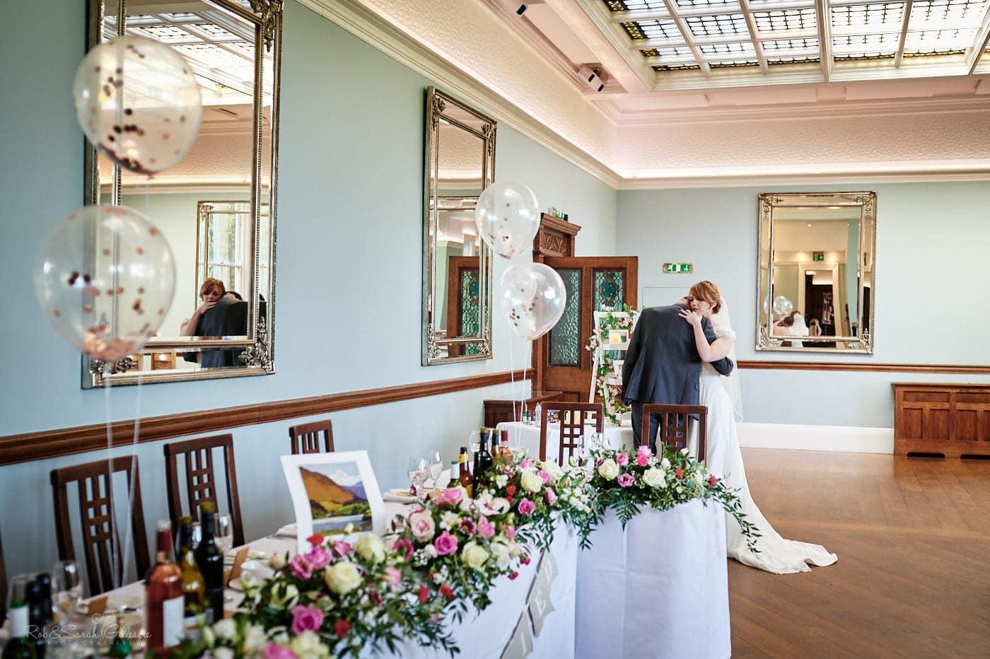 Bride hugs groom in ballroom at Pendrell Hall