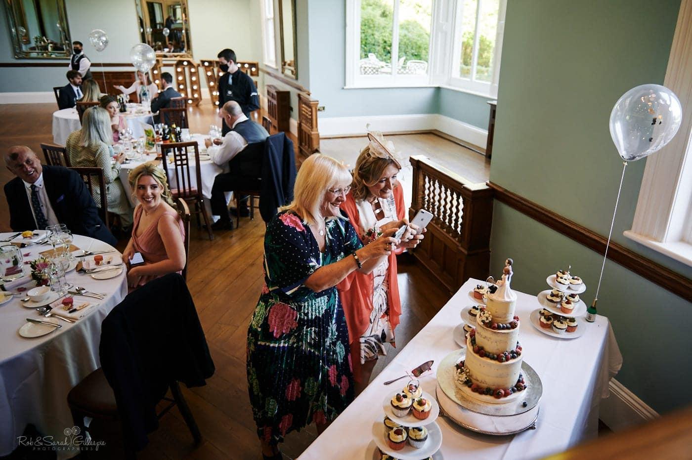 Wedding guests take photos of wedding cake
