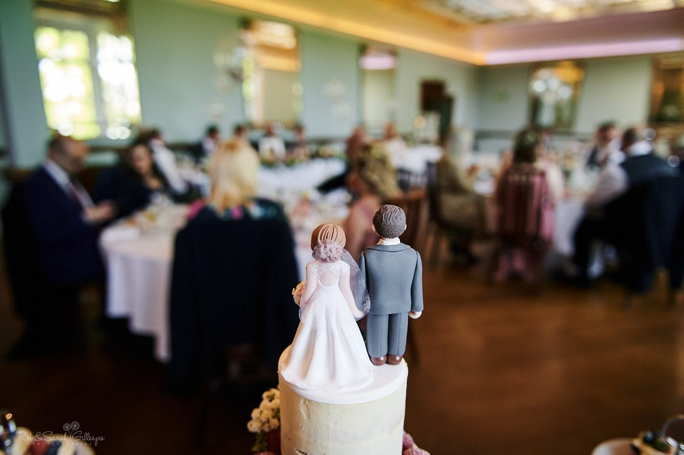 Wedding cake topper with wedding meal taking place in background