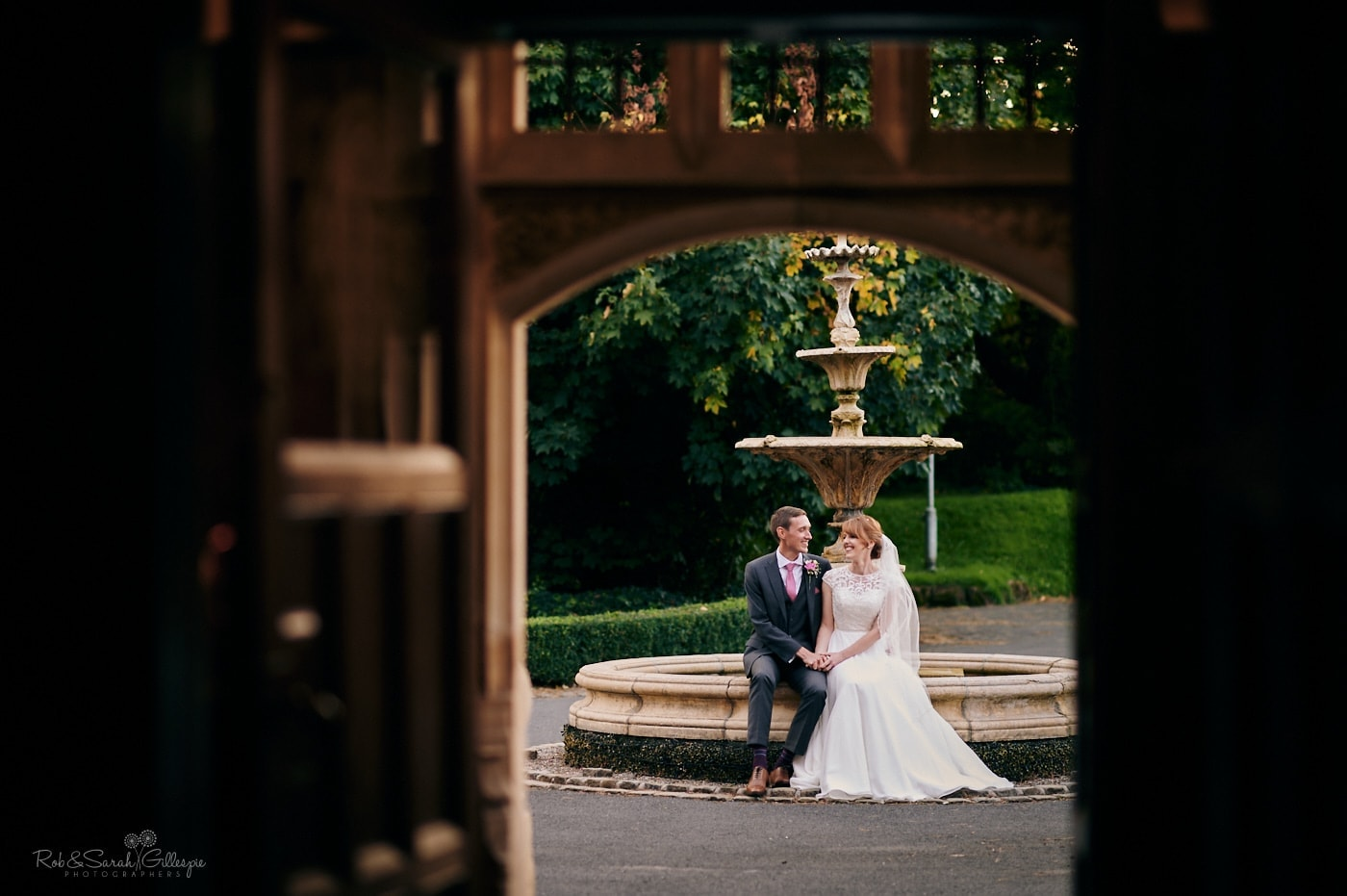 View from inside Pendrell Hall as bride and groom sit on edge of stone fountain