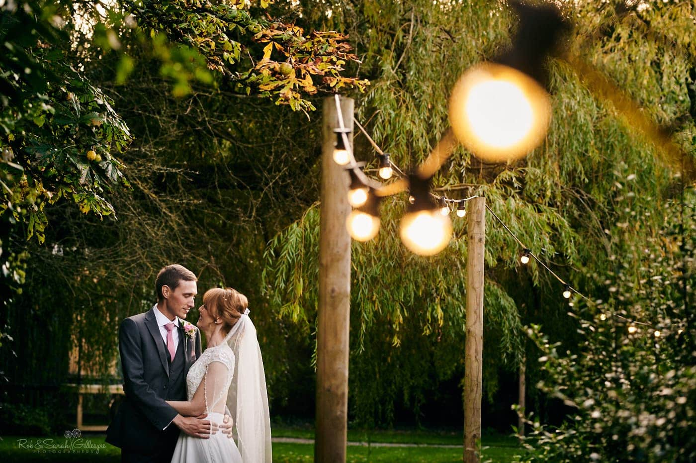Bride and groom in gardens at Pendrell Hall with trees and festoon lights