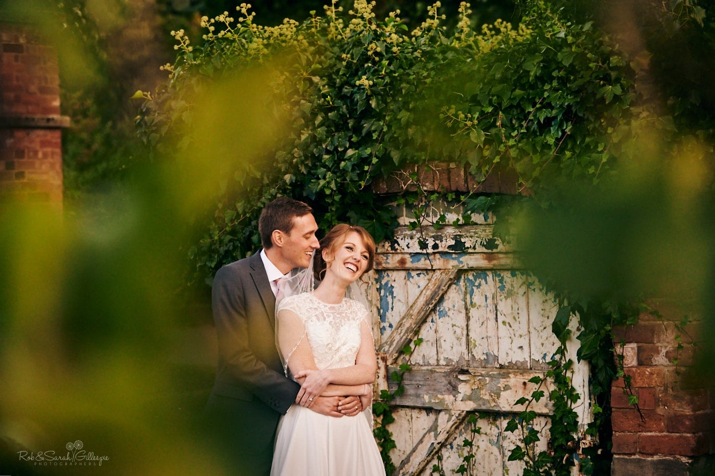 Bride and groom near old gate in Pendrell Hall gardens
