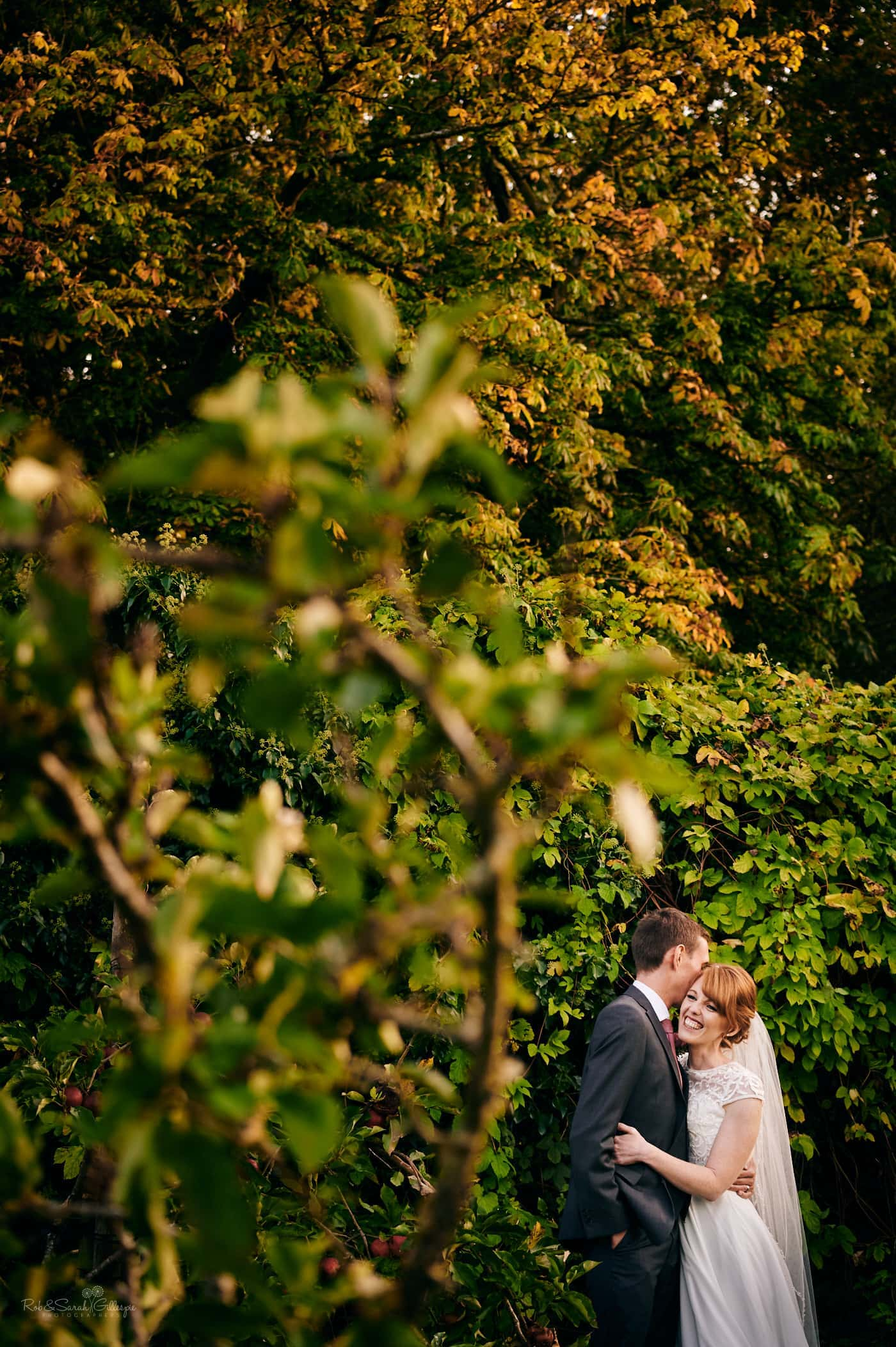 Bride and groom relaxing together in gardens with beautiful evening light