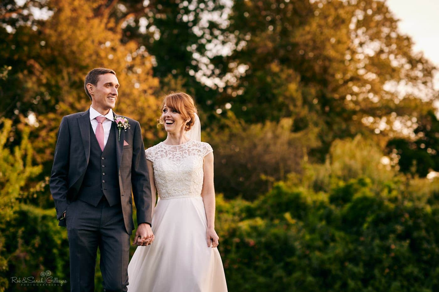 Newly married couple walk holding hands through Pendrell Hall gardens