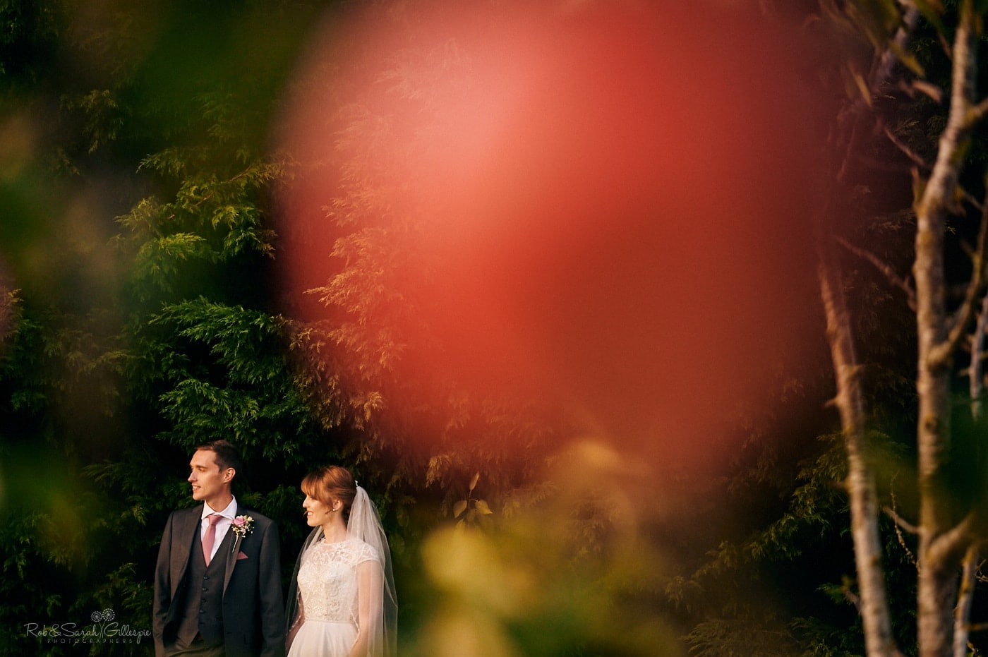 Bride and groom in gardens with red apple in foreground