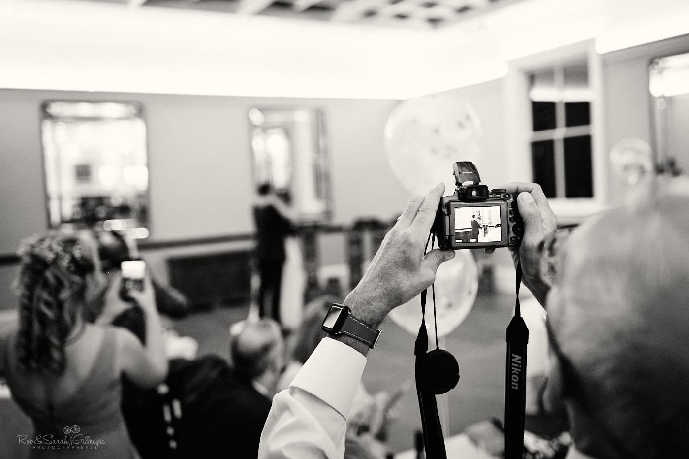 Wedding guests takes photo of bride and groom's first dance