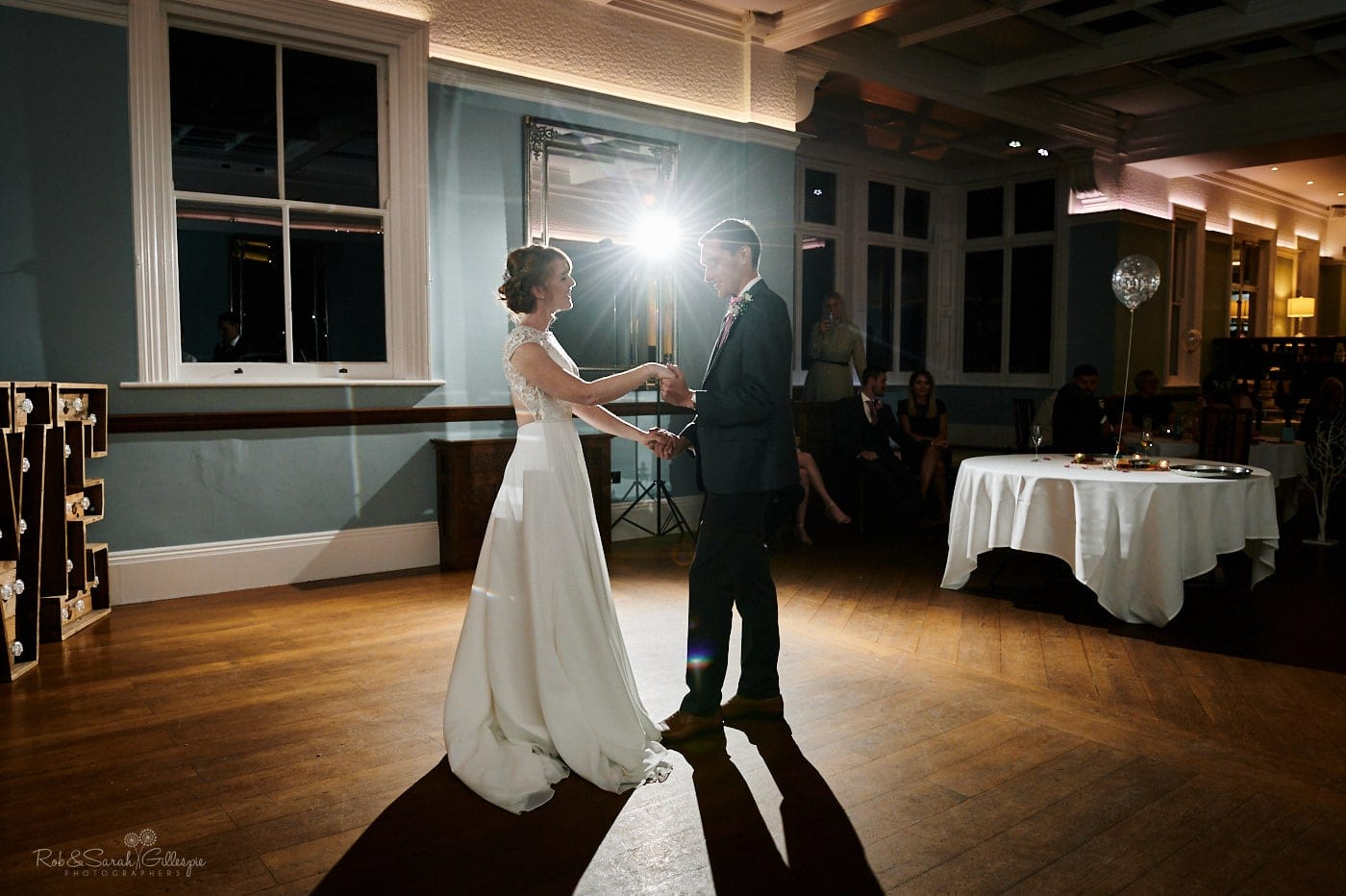 Bride and groom first dance as guests watch