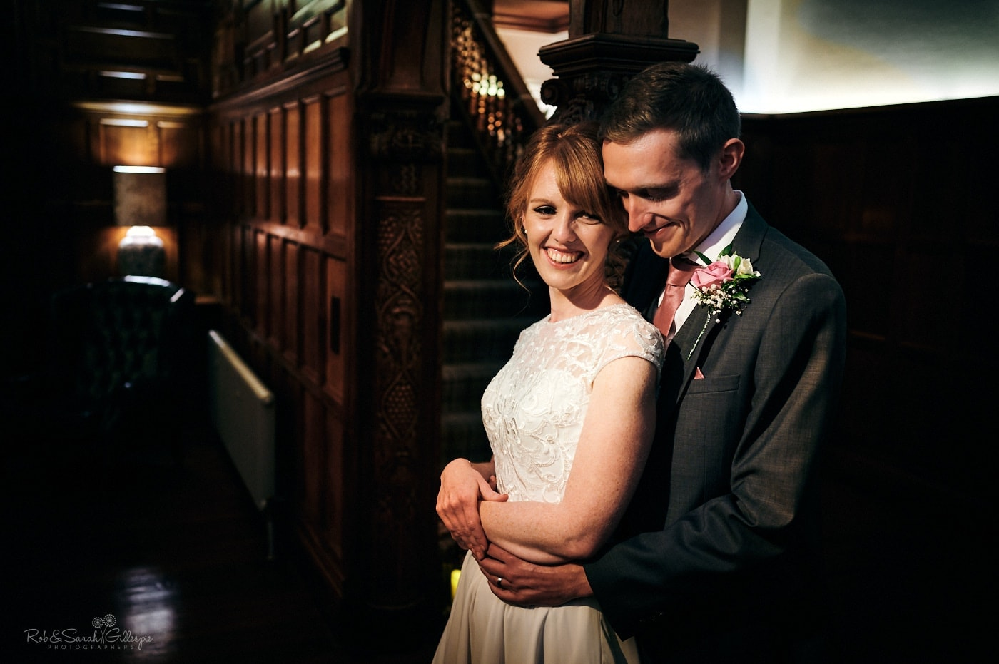 Bride and groom cuddle in dimly-lit panelled room at Pendrell Hall