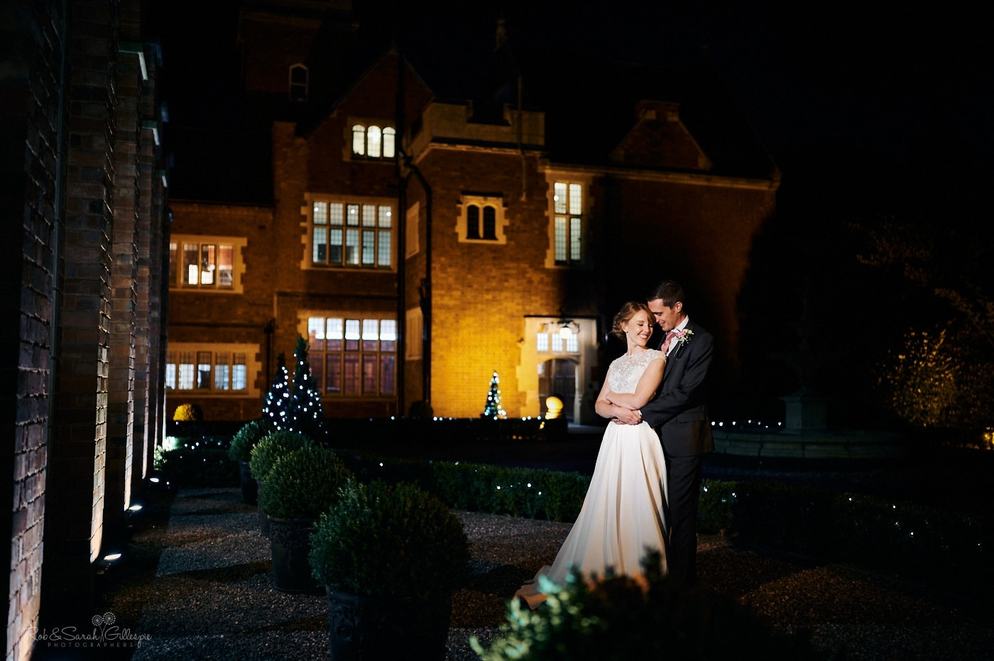 Bride and groom outside Pendrell Hall at night with lights