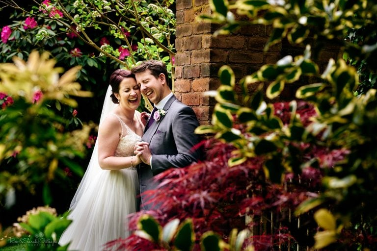 Bride and groom laughing together in gardens at Pendrell Hall