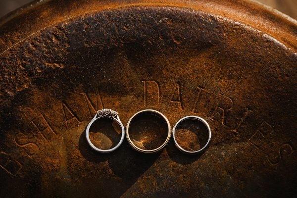 Detail of wedding and engagement rings on top of rusty barrel in beautiful golden light