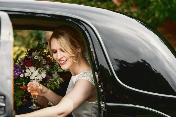 Bride holding champagne glass gets out of wedding car, smiling