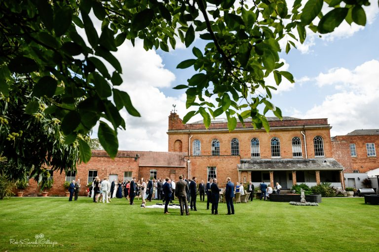 St Annes Hall gardens at Stanbrook Abbey, with wedding guests relaxing during drinks reception