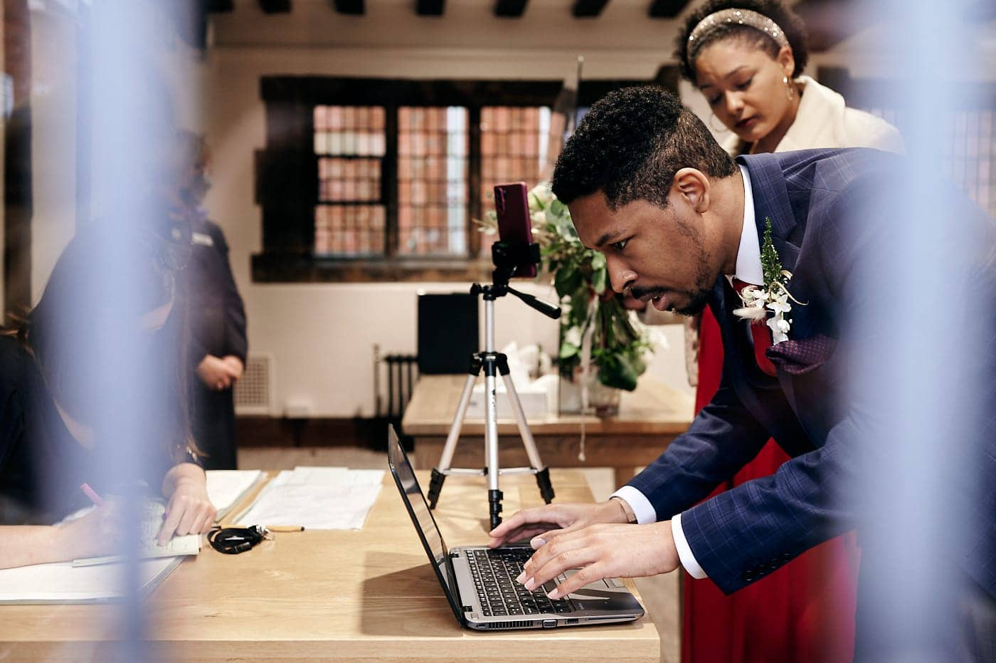 Groom sets up laptop for livestreaming of wedding ceremony in The Henley Room
