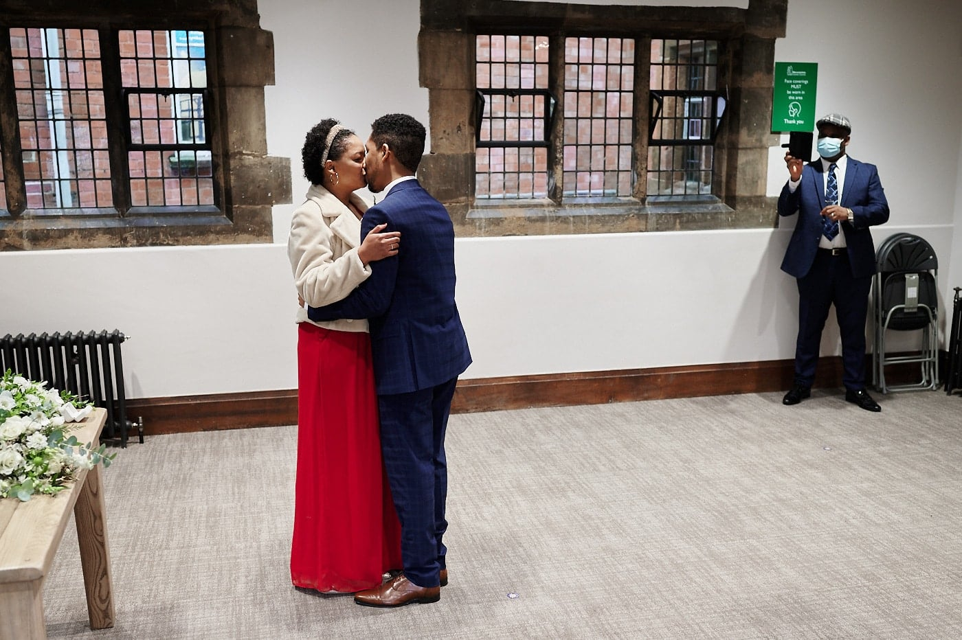 First kiss during wedding ceremony in The Henley Room as witness with mask takes photo