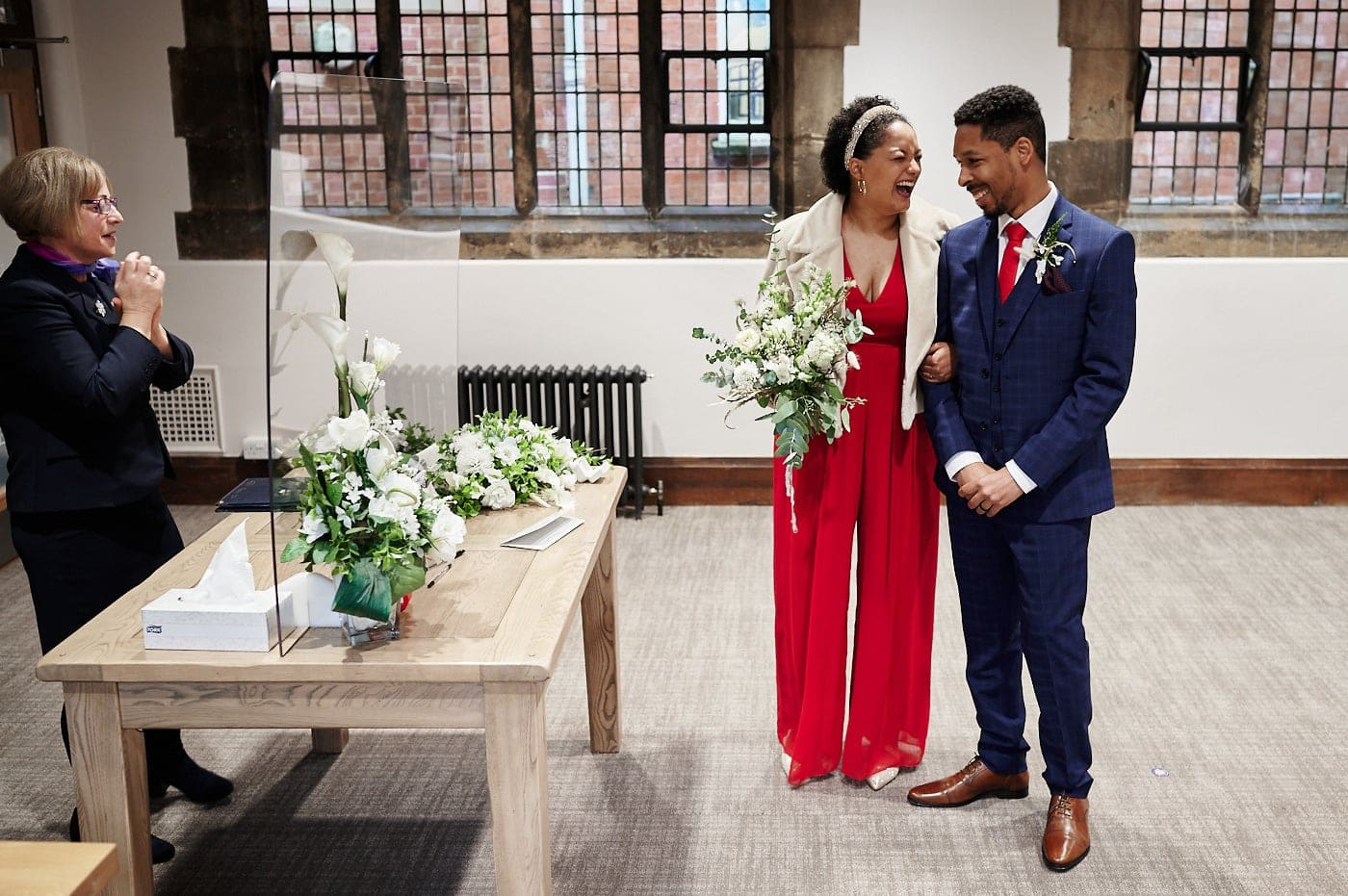Bride and groom laughing during wedding ceremony in The Henley Room