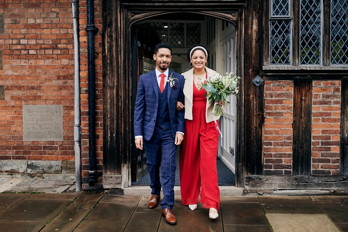 Bride and groom walk out of The Henley Room in Stratford-upon-Avon after small wedding ceremony