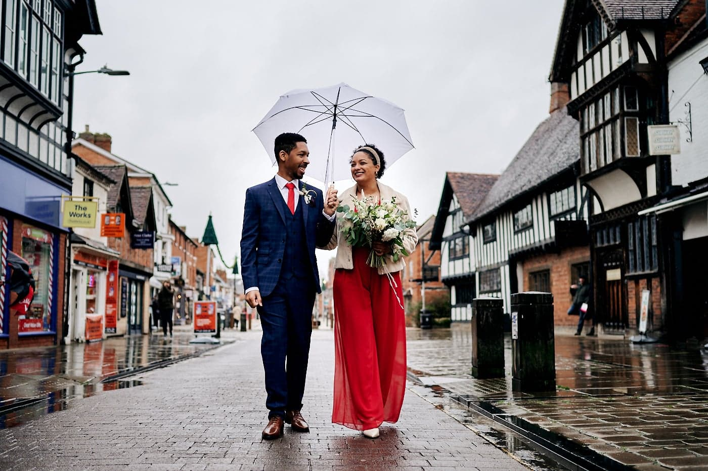 Bride in red trouser suit and groom in blue suit walk under umbrella through streets of Stratford-upon-Avon