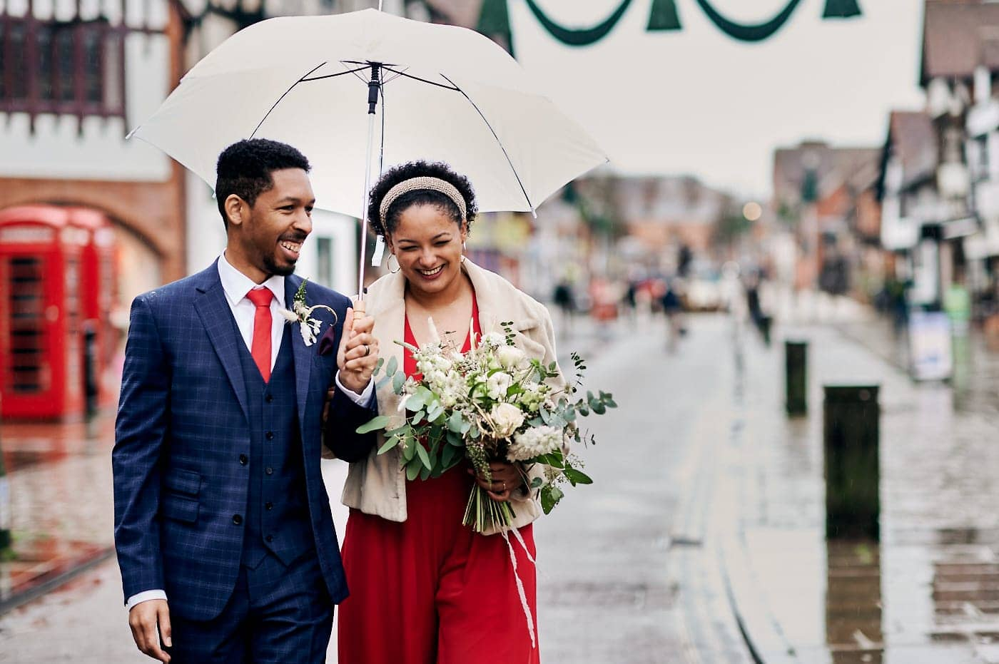 Newly married couple laughing as they walk together in Stratford-upon-Avon