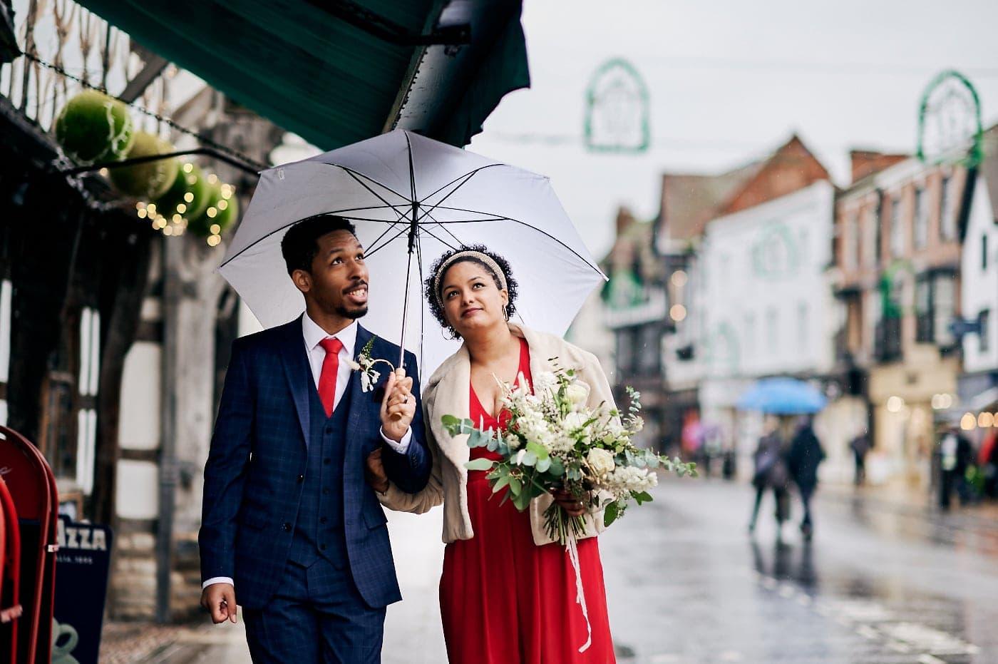 Bride and groom under umbrella as they walk through Stratford-upon-Avon streets