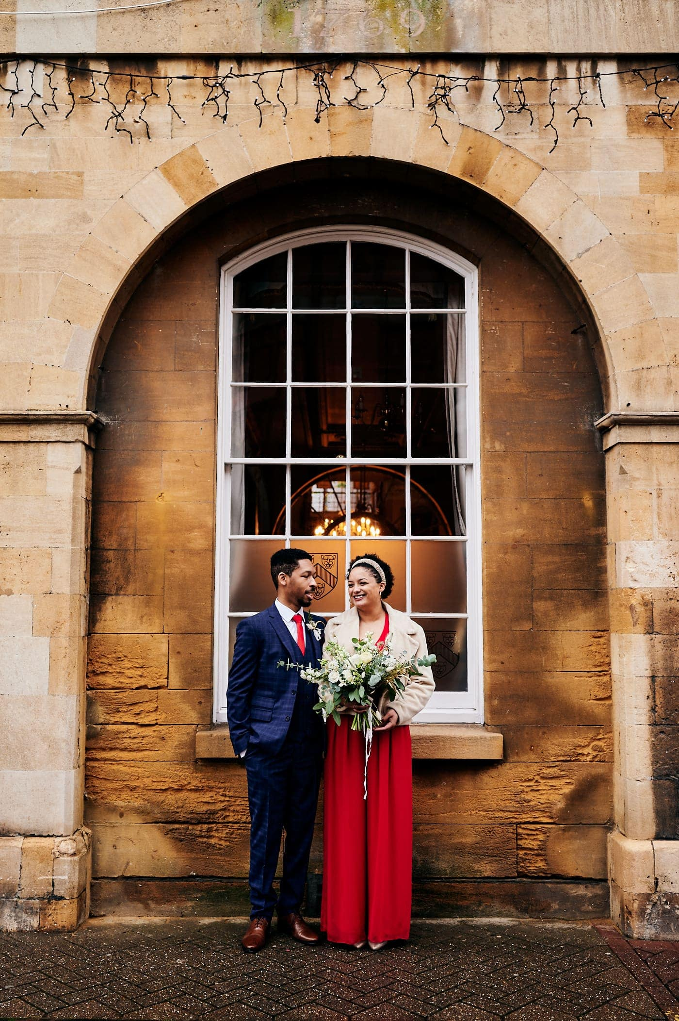 Bride and groom under archway in Stratford-upon-Avon