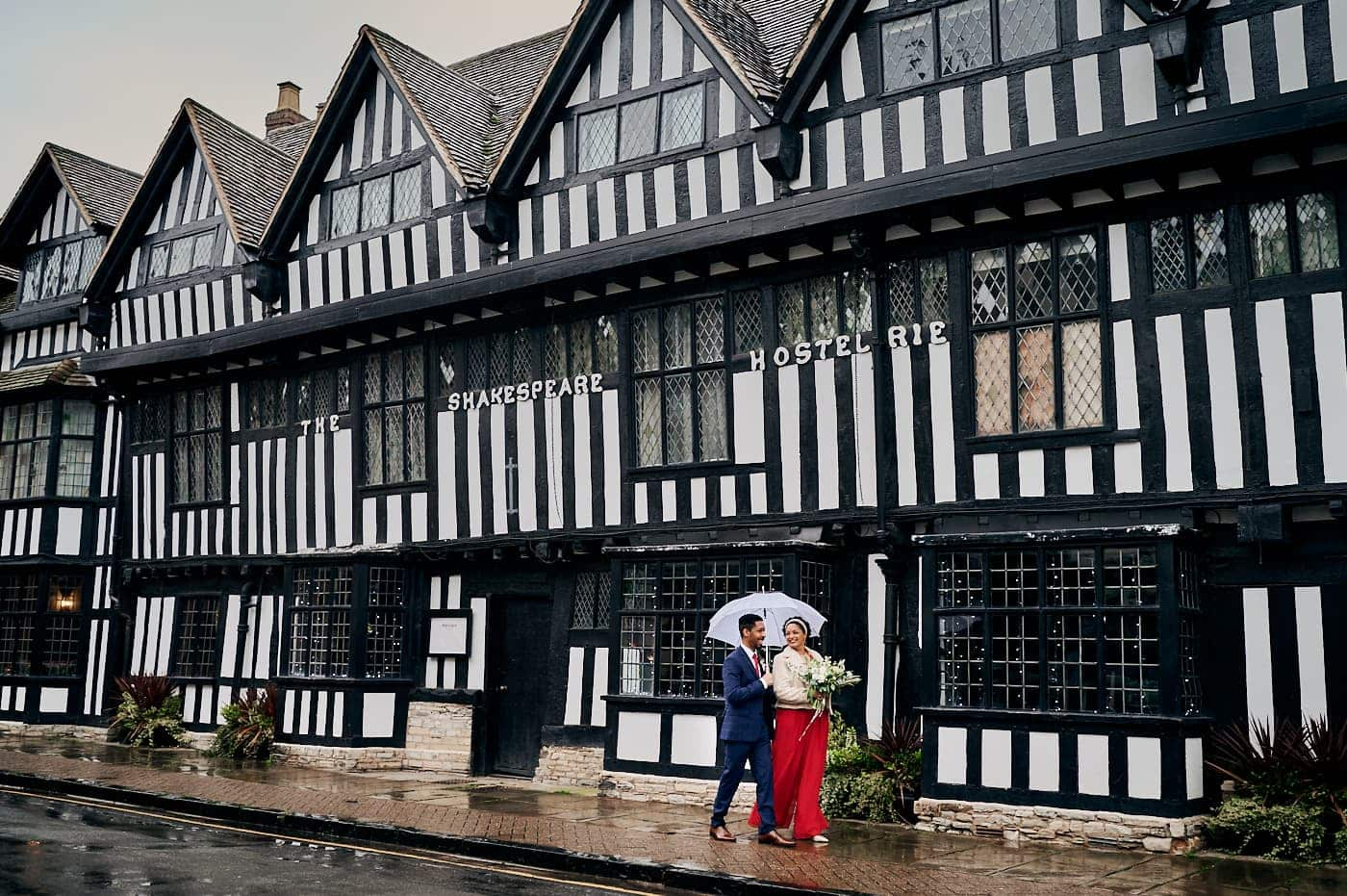 Newly married couple walk in front of old hostel in Stratford-upon-Avon