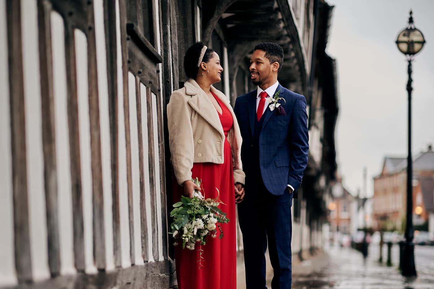 Bride and groom holding hands next to old half-timber building in Stratford-upon-Avon