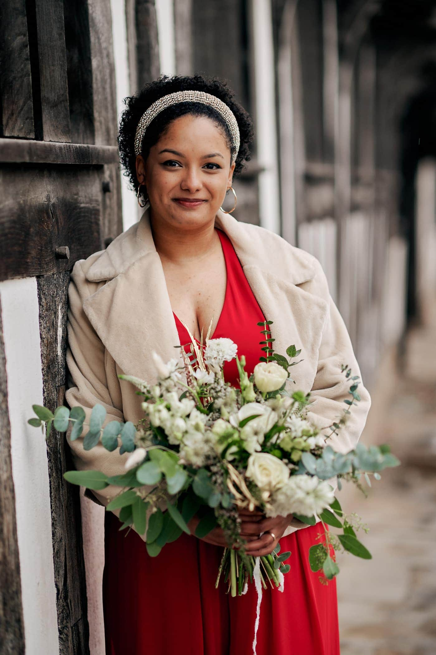 Portrait of bride in red trouser suit holding beautiful bouquet of flowers