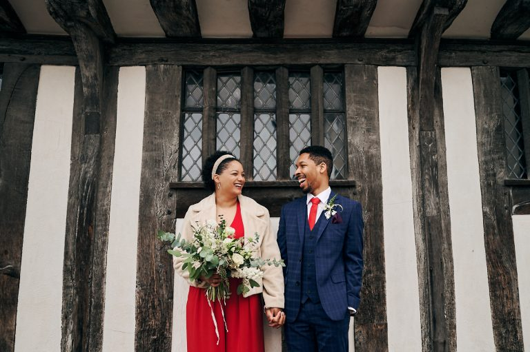 Bride and groom laughing together in front of old building in Stratford-upon-Avon