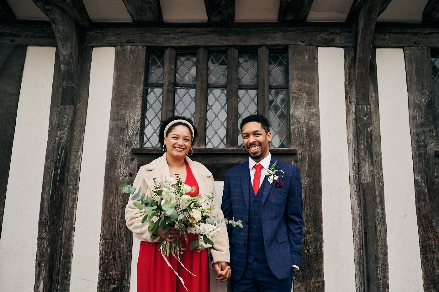 Bride and groom happy and smiling in front of old half-timber building in Stratford-upon-Avon