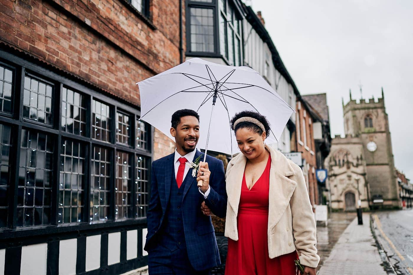 Bride and groom happy and smiling as they walk together in Stratford-upon-Avon
