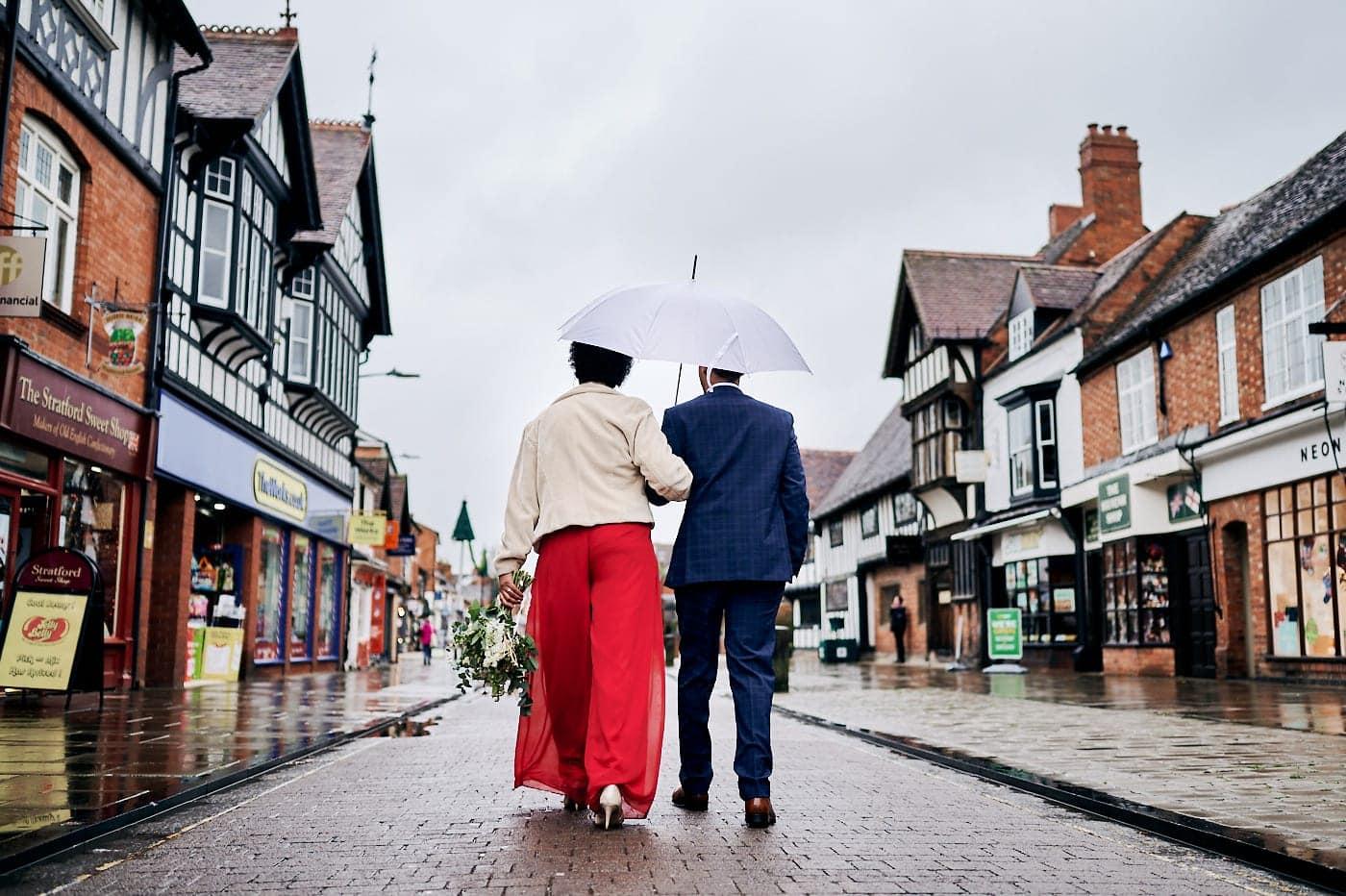 Newly married couple walk arm in arm under umbrella through street in Stratford-upon-Avon