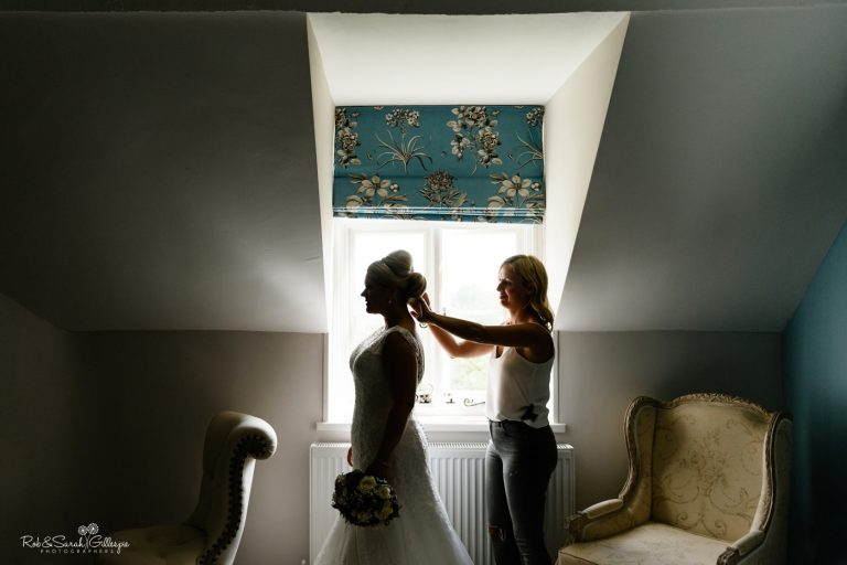 Bride silhouetted against window as she has hair adjusted by stylist