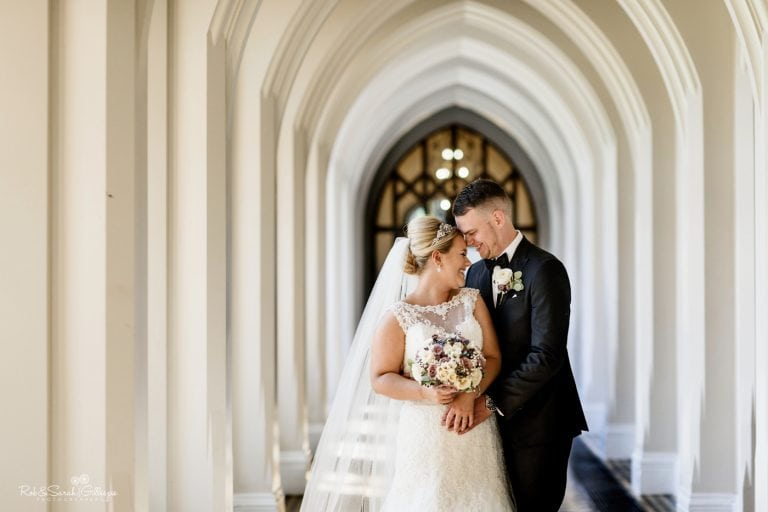 Newly married couple laughing together in cloister corridors at Stanbrook Abbey